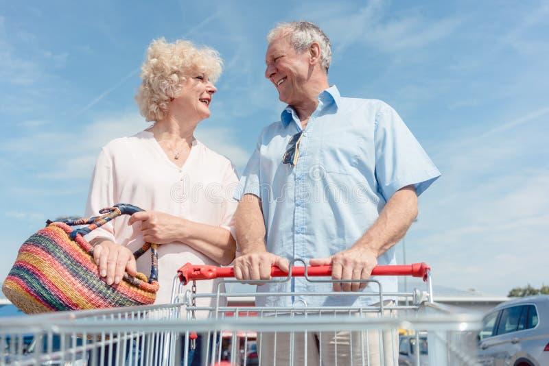 Hombre mayor que sostiene un carro de la compra mientras que mira a su esposa con amor fotografía de archivo libre de regalías