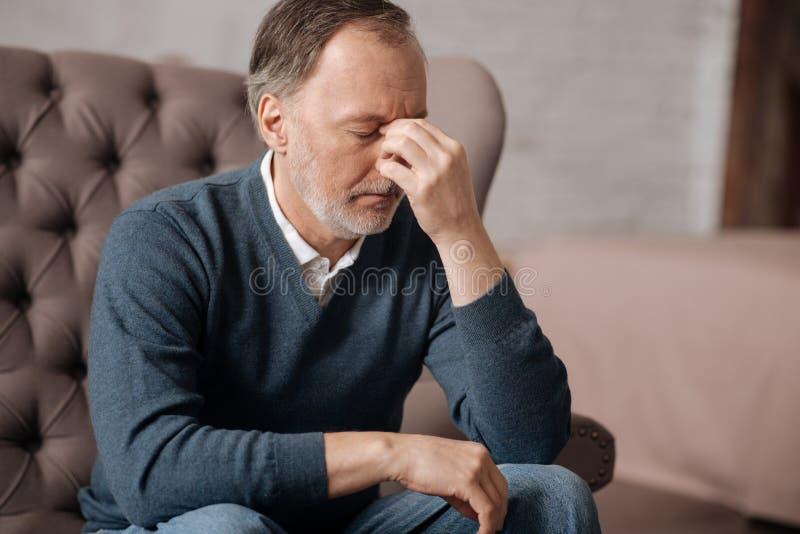 Hombre mayor que tiene dolor de cabeza realmente terrible fotos de archivo libres de regalías