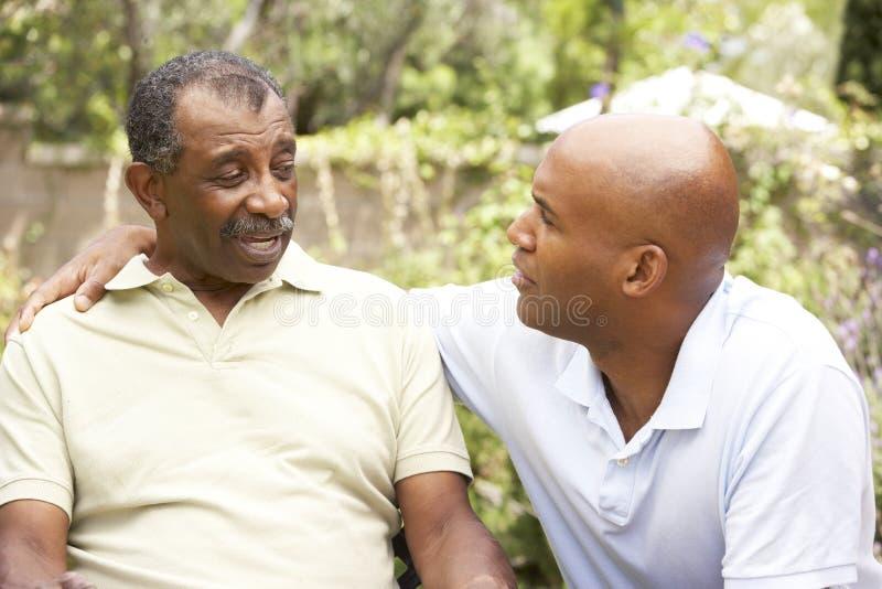 Hombre mayor que tiene el hijo serio del adulto de la conversación foto de archivo libre de regalías
