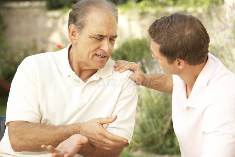 Hombre mayor que tiene el hijo serio del adulto de la conversación imagen de archivo