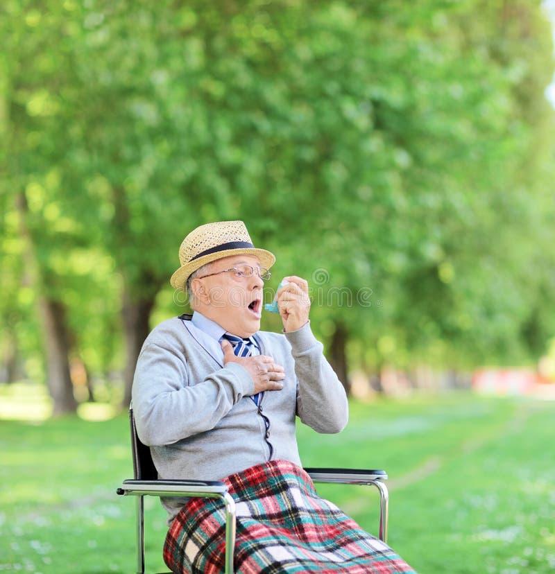 Hombre mayor que tiene un ataque de asma en parque fotos de archivo libres de regalías
