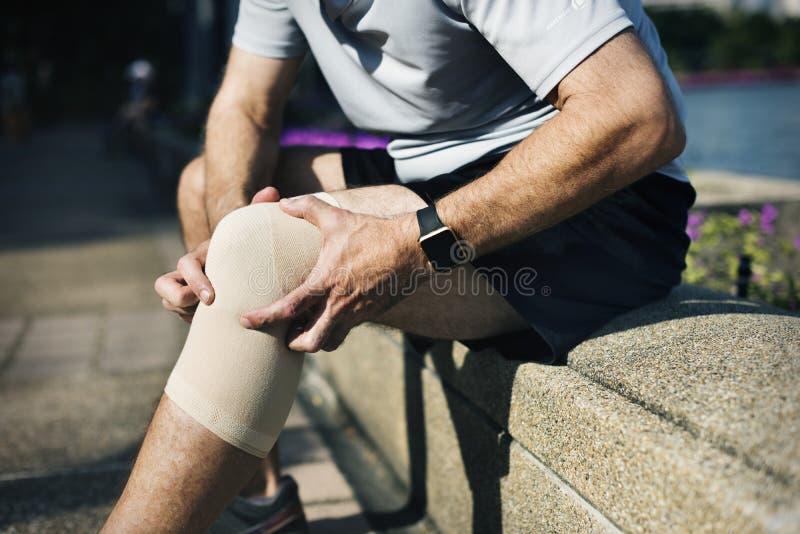 Hombre mayor que tiene una lesión de rodilla fotografía de archivo