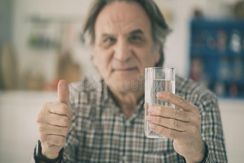 Hombre mayor que tiene vidrio de agua y que muestra su pulgar en kitche foto de archivo libre de regalías