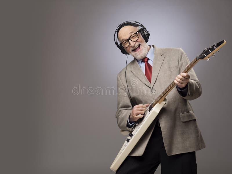 Hombre mayor que toca la guitarra eléctrica fotografía de archivo