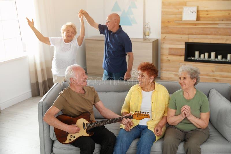 Hombre mayor que toca la guitarra para sus amigos imagenes de archivo