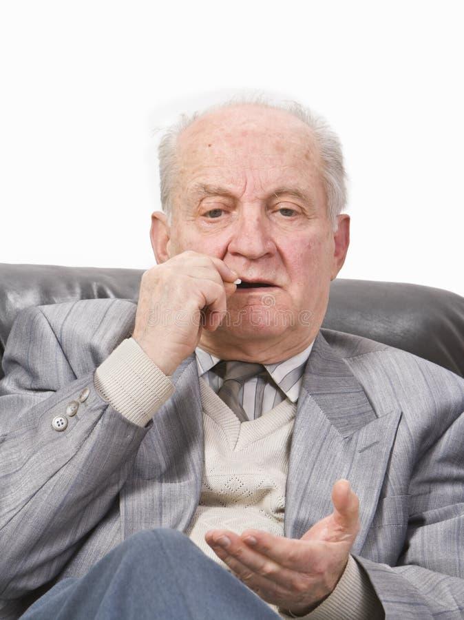 Hombre mayor que toma la medicación foto de archivo