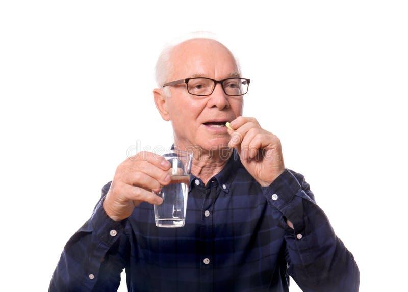 Hombre mayor que toma la medicina contra el fondo blanco foto de archivo libre de regalías