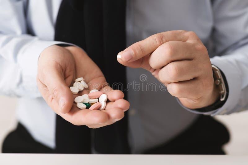Hombre mayor que toma las píldoras, sosteniendo el montón de la medicina fotos de archivo libres de regalías