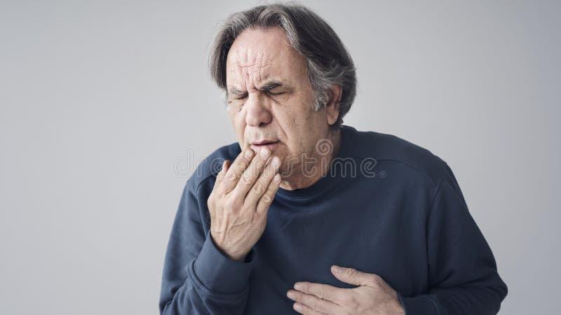 Hombre mayor que tose en fondo aislado foto de archivo libre de regalías
