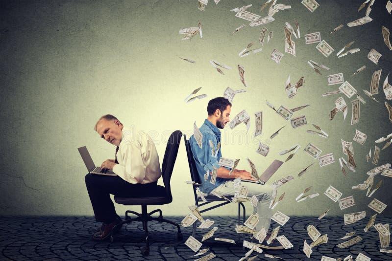Hombre mayor que trabaja en el ordenador portátil que se sienta al lado del individuo joven que usa el ordenador debajo de la llu fotografía de archivo libre de regalías