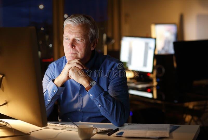 Hombre mayor que trabaja tarde fotografía de archivo