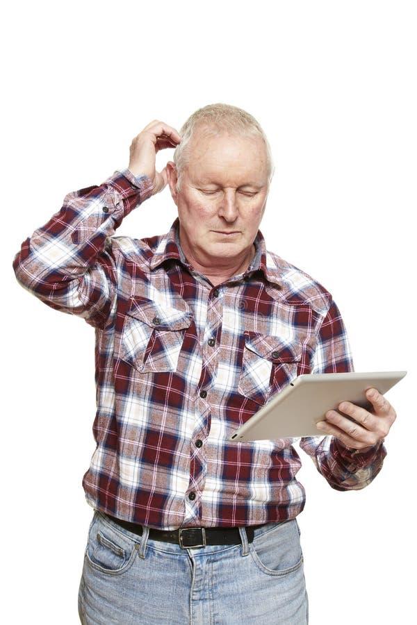 Hombre mayor que usa el ordenador de la tableta que parece confundido fotos de archivo