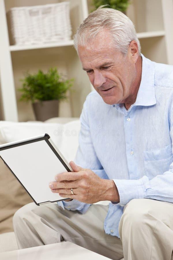 Hombre mayor que usa el ordenador de la tablilla en el país fotos de archivo libres de regalías