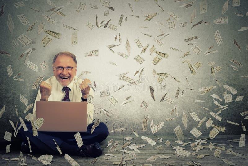 Hombre mayor que usa el ordenador portátil que construye el negocio en línea que hace los billetes de dólar del dinero que caen a imágenes de archivo libres de regalías