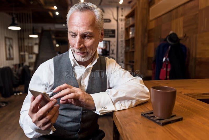 Hombre mayor que usa el teléfono móvil en el contador de la barra imagenes de archivo