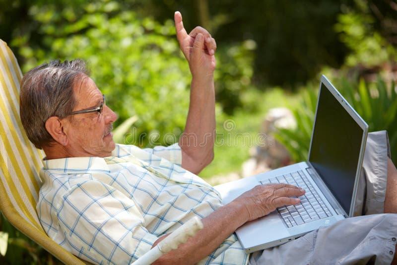 Hombre mayor que usa la computadora portátil al aire libre fotografía de archivo libre de regalías