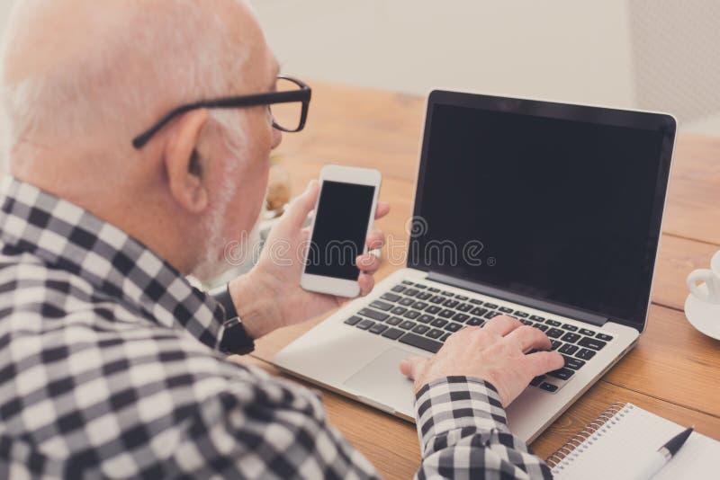 Hombre mayor que usa la maqueta del ordenador portátil y del smartphone imágenes de archivo libres de regalías