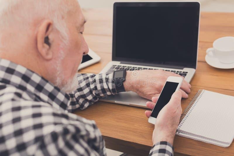 Hombre mayor que usa la maqueta del smartphone imagen de archivo libre de regalías