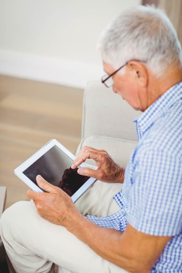 Hombre mayor que usa la tableta digital fotos de archivo