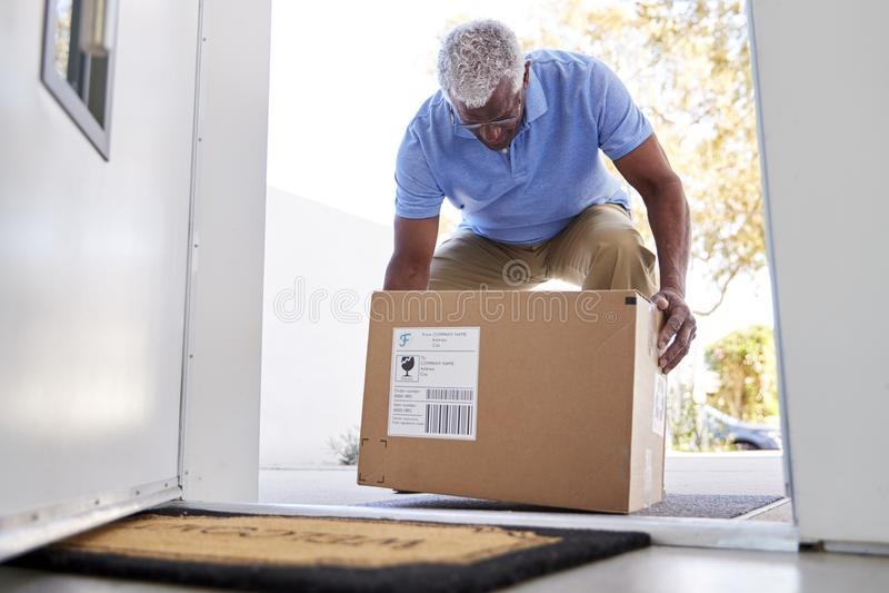 Hombre mayor que vuelve al servicio a domicilio en caja de cartón fuera de Front Door foto de archivo