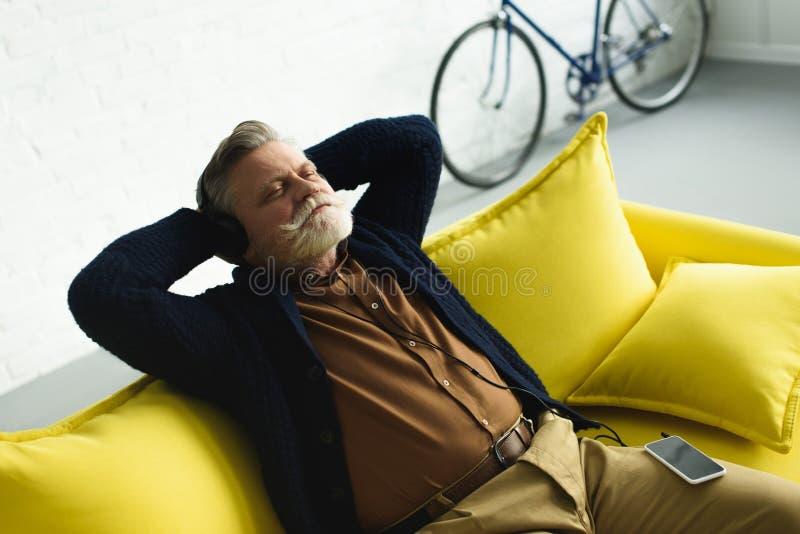 hombre mayor relajado en los auriculares que se sientan con las manos detrás de la cabeza en el sofá y la música que escucha fotos de archivo libres de regalías