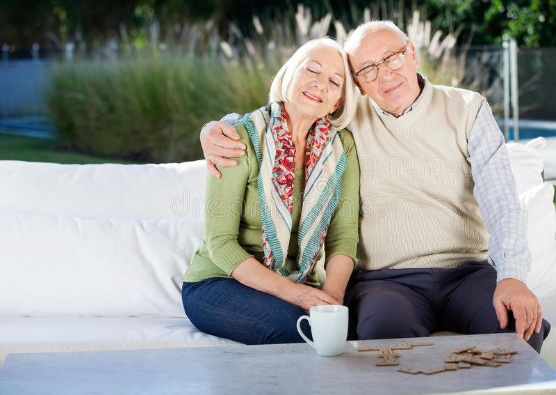 Hombre mayor relajado que se sienta en el sofá en el oficio de enfermera imágenes de archivo libres de regalías