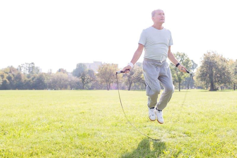 Hombre mayor resuelto que se resuelve con la cuerda que salta en parque imagen de archivo