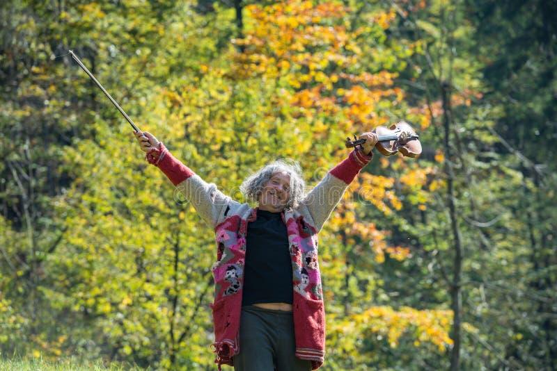 Hombre mayor sin hogar feliz en suéter rasgado que disfruta de vida fotos de archivo libres de regalías