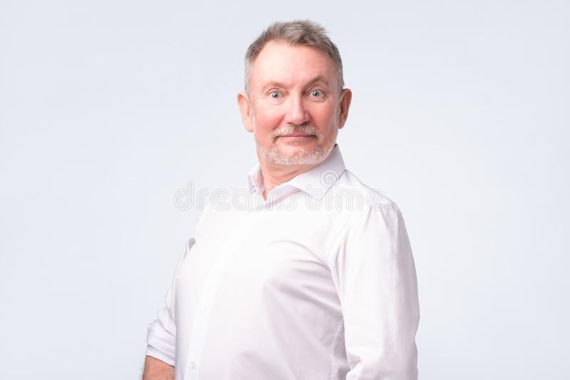 Hombre mayor sonriente en la situación blanca de la camisa y sonrisa en la sensación de la cámara buena fotografía de archivo libre de regalías