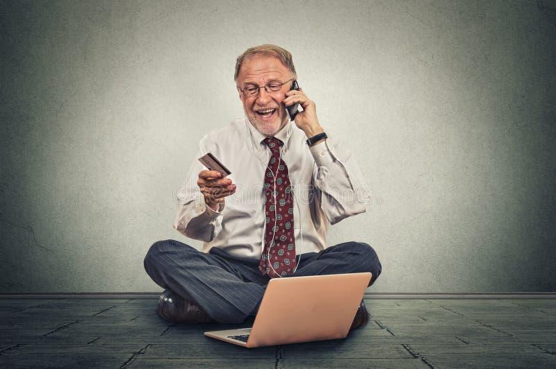 Hombre mayor sonriente que hace orden por el teléfono móvil que se sienta en un piso de su oficina imagen de archivo
