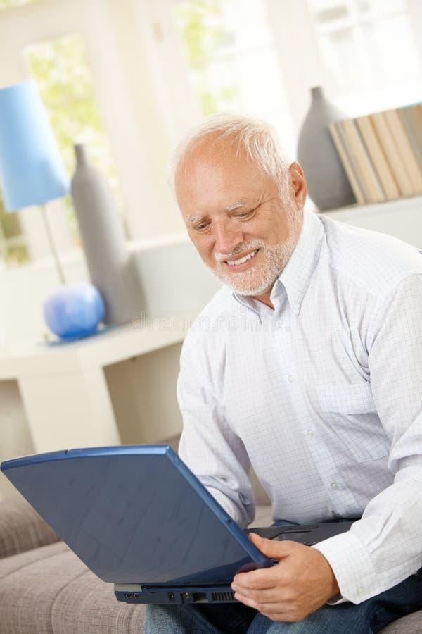 Hombre mayor sonriente que mira la pantalla de ordenador fotos de archivo libres de regalías
