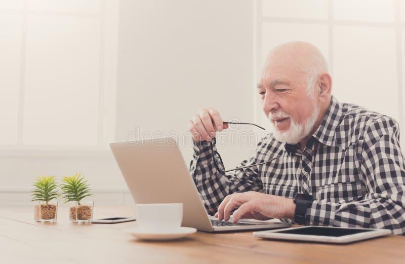 Hombre mayor sonriente que usa el espacio de la copia del ordenador portátil imagen de archivo