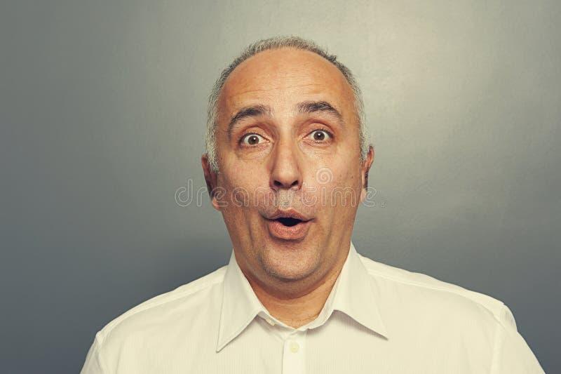 Hombre mayor sorprendido sobre gris imagen de archivo libre de regalías