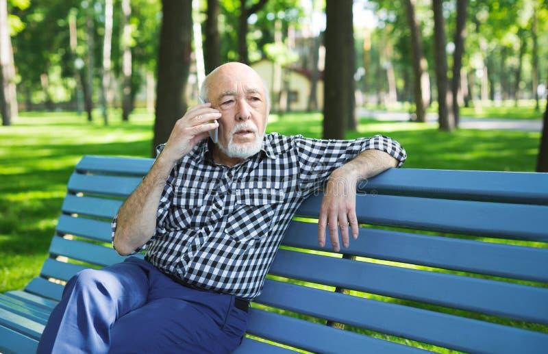 Hombre mayor triste con el móvil al aire libre foto de archivo