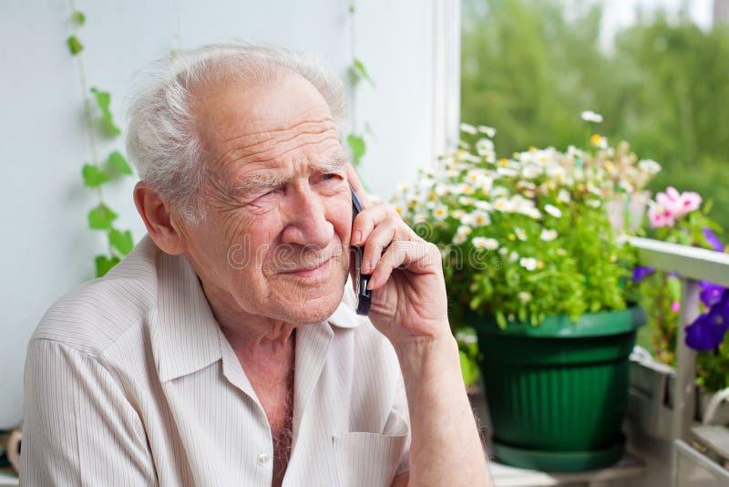 Hombre mayor triste con el teléfono imagenes de archivo
