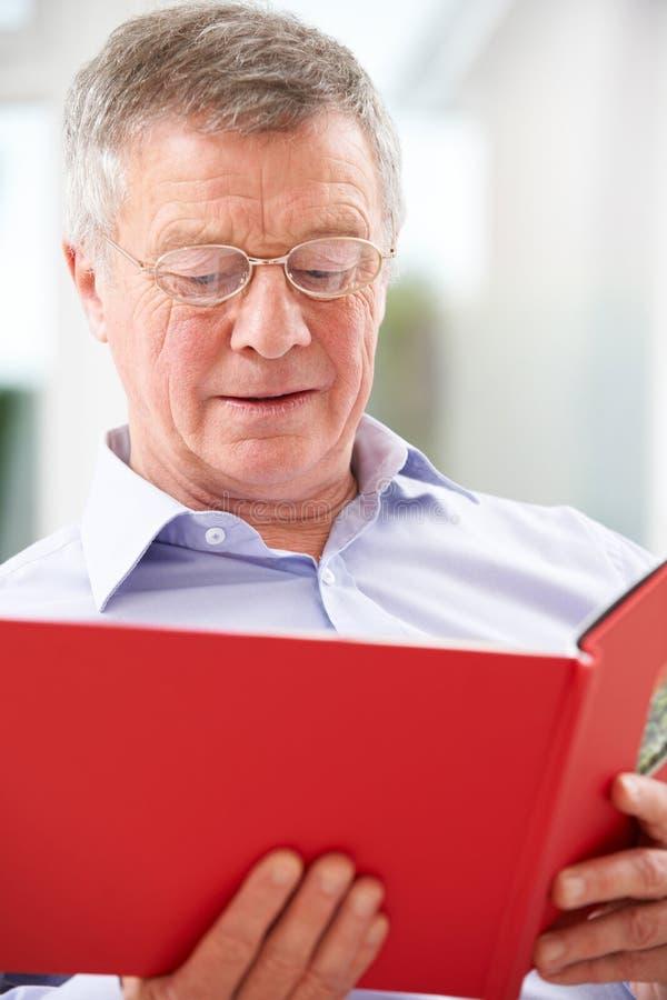 Hombre mayor triste que mira el álbum de foto fotografía de archivo