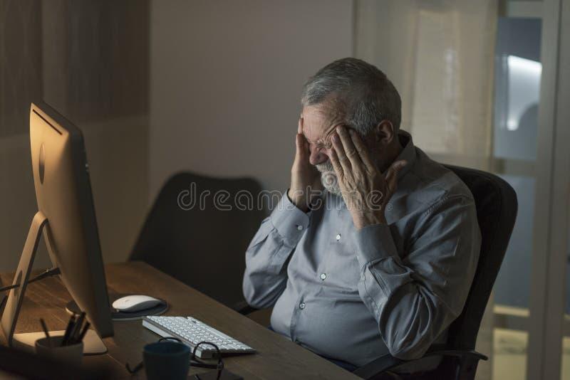 Hombre mayor triste solo que conecta en la noche imagenes de archivo
