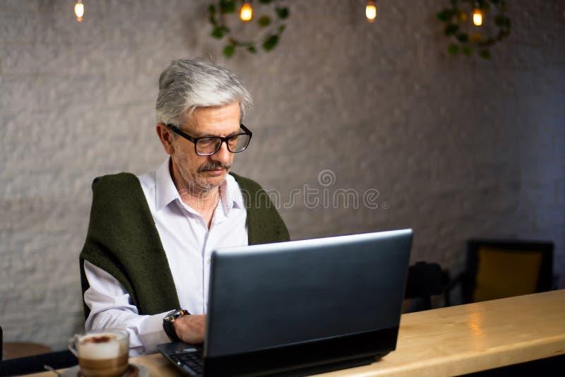 Hombre mayor usando el ordenador portátil y el café el tener en la barra imagen de archivo
