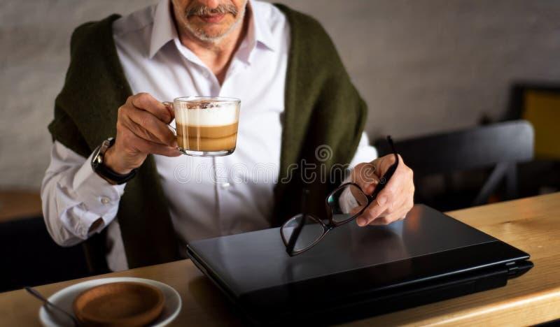 Hombre mayor usando el ordenador port?til y el caf? el tener en la barra imagenes de archivo