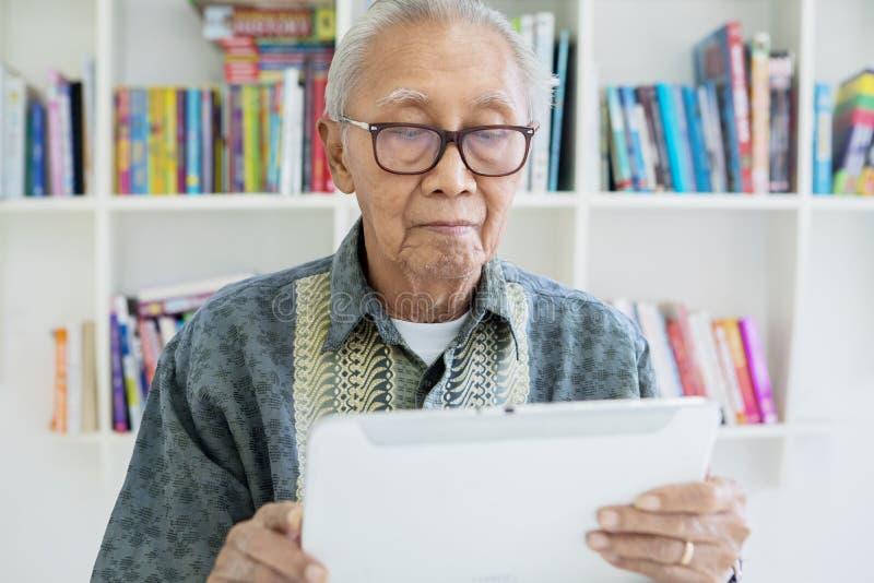 Hombre mayor usando la tableta digital en la biblioteca foto de archivo libre de regalías