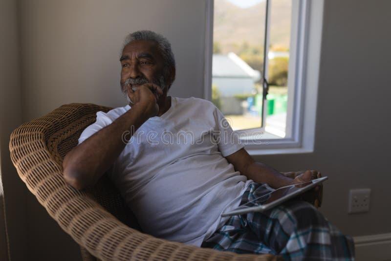 Hombre mayor usando la tableta digital en dormitorio en casa imagen de archivo