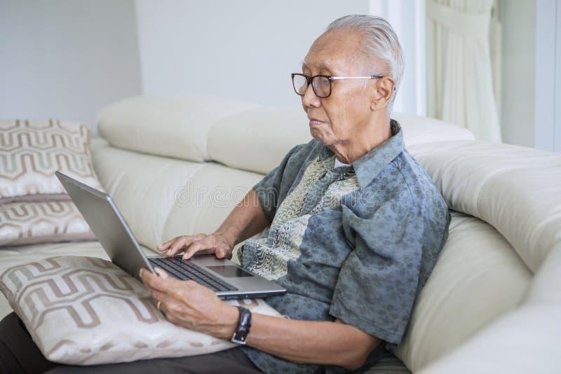 Hombre mayor usando un ordenador portátil en casa imágenes de archivo libres de regalías