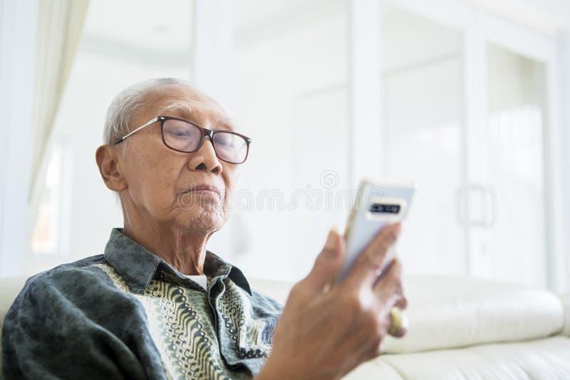 Hombre mayor usando un smartphone en casa fotos de archivo
