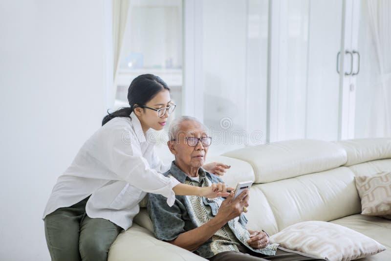 Hombre mayor usando un teléfono con su hija imágenes de archivo libres de regalías