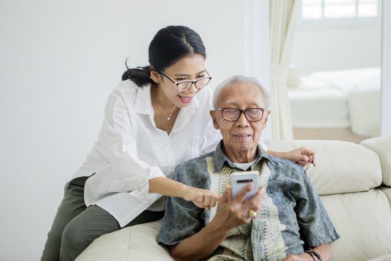 Hombre mayor usando un teléfono con su hija fotos de archivo