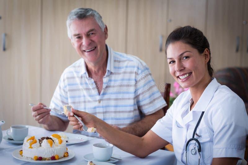 Hombre mayor y doctor de sexo femenino que hablan mientras que teniendo torta en sala de estar imagenes de archivo