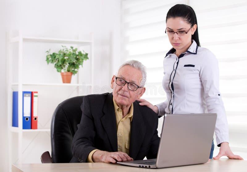 Hombre mayor y muchacha en la oficina imagenes de archivo