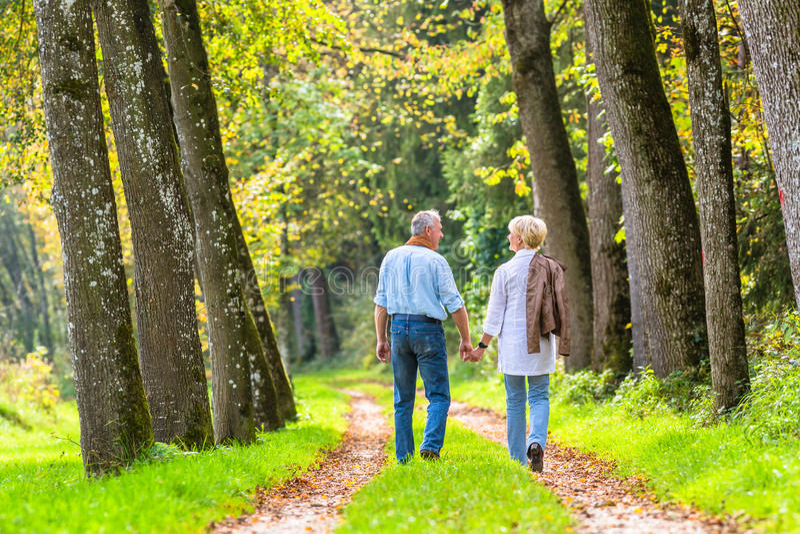 Hombre mayor y mujer que celebran caminar de la mano imagen de archivo