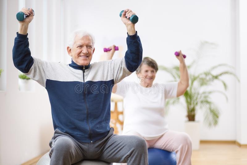 Hombre mayor y mujer que ejercitan en bolas gimnásticas durante la sesión de la fisioterapia en el hospital imagen de archivo
