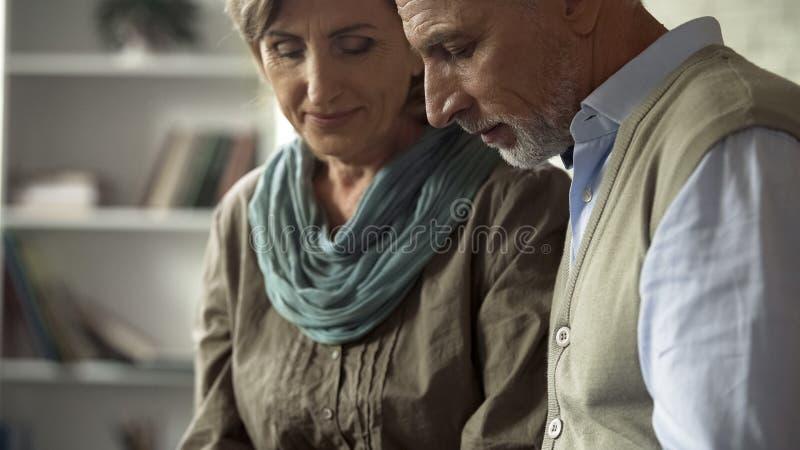 Hombre mayor y mujer que se sientan junto en el sofá, felicidad acertada del matrimonio foto de archivo